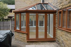 A conservatory installation using brick base and oak colour uPVC windows and doors