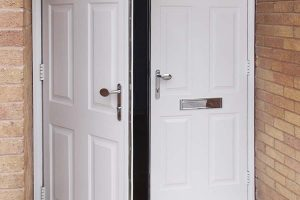 Double door entrance door in white with chrome handles and letterplate