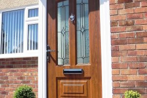 Oak effect composite door with two glazed panels and polished chrome hardware