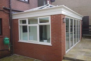 Side on view of completed orangery with brick base and uPVC roof, windows and doors