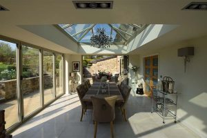 An orangery with a large dining room table and large glass roof